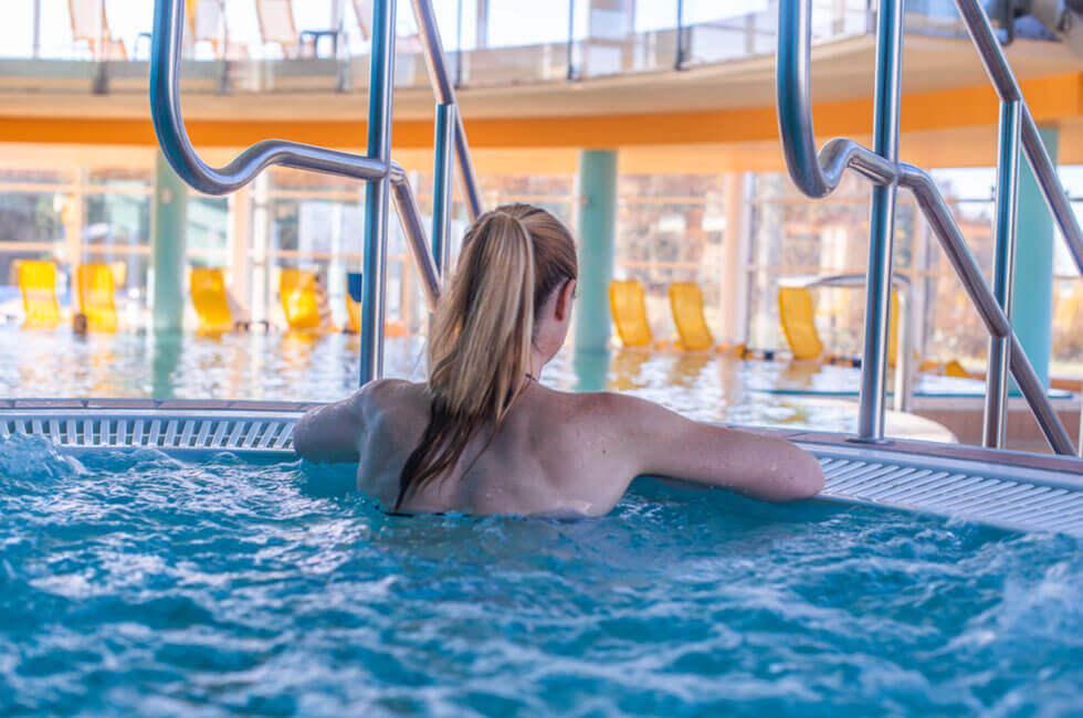 Genießen Sie das warme Wasser des Whirlpools im großzügigen Innenbereich der Poollandschaft
