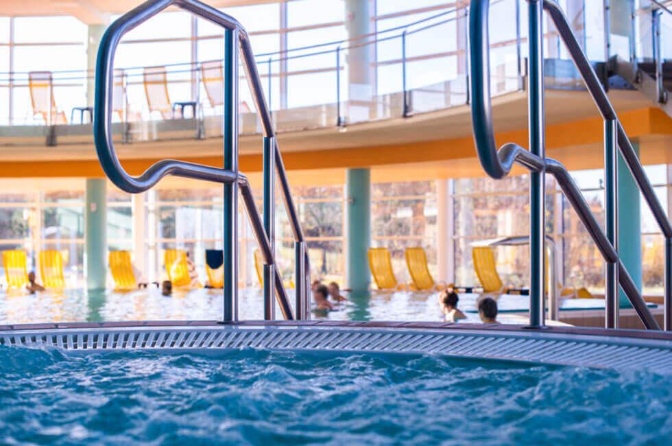 Weitläufiges Hotel-Schwimmbad mit Whirlpool und Sonnengalerie für einen entspannten Gesundheits- und Wellnessurlaub